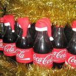 Бутылки кока-колы в новогодних крышечках-шапочках.